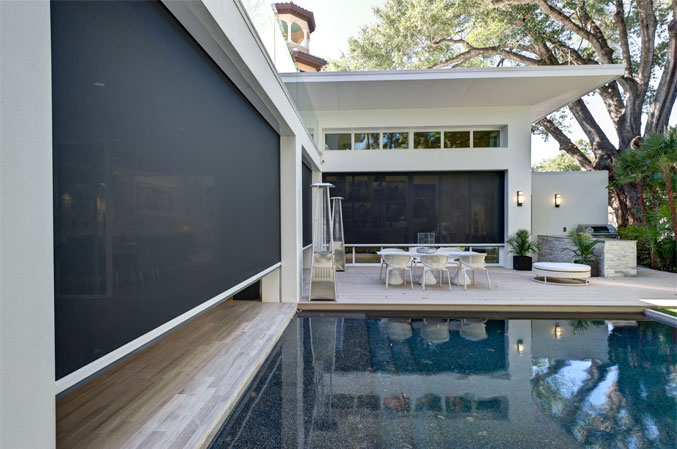 outdoor space with outdoor screens around pool